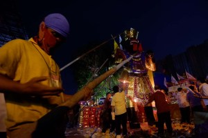 Patung Dewa Penguasa Akhirat diarak ke halaman untuk dibakar.